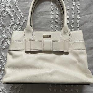 Cream Kate Spade bag with black/white polka dot interior lining